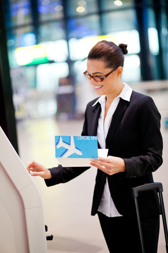 happy businesswoman using self help check in machine at airport