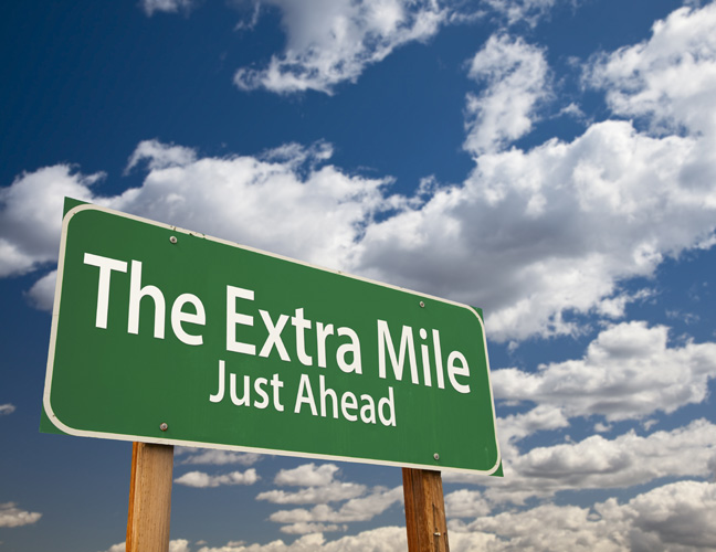 The Extra Mile Just Ahead Green Road Sign Over Dramatic Clouds a